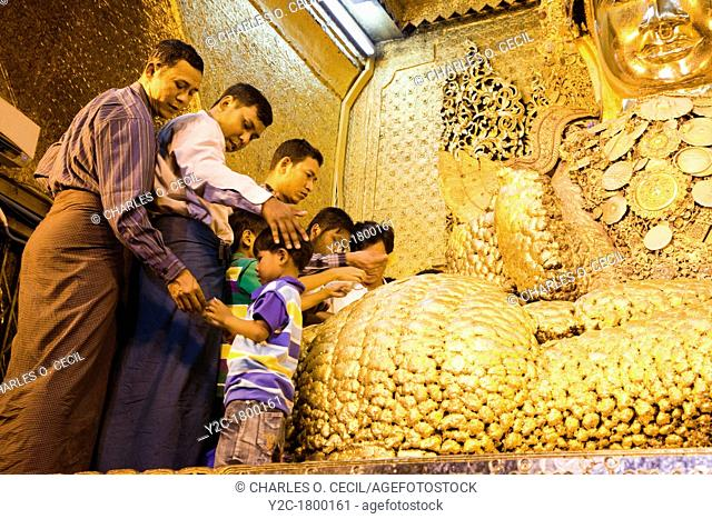 Myanmar, Burma  Mandalay  Mahamuni Buddhist Temple  Men and boys apply gold leaf to Buddha statue  Only males are allowed to approach the Mahamuni Buddha