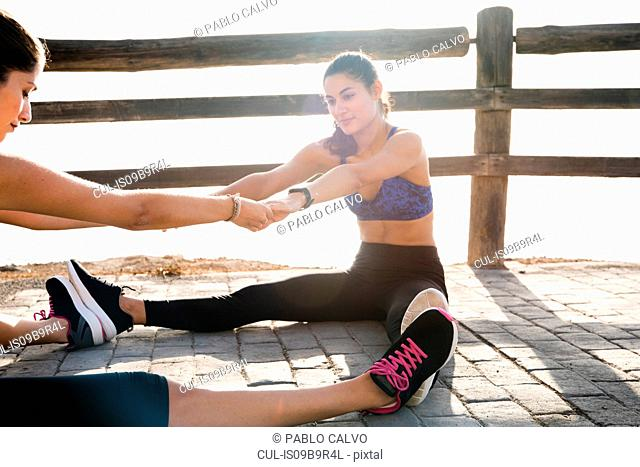 Two young women training together on sea waterfront