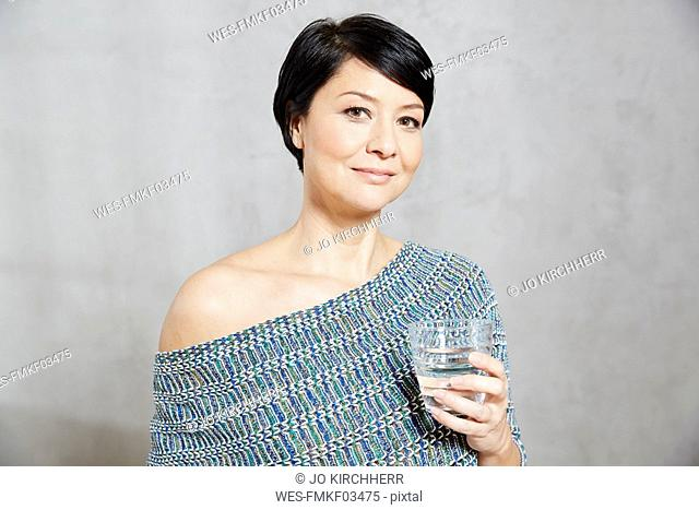 Portrait of confident woman holding glass of water