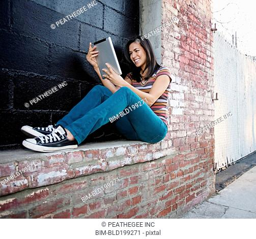 Mixed race woman using digital tablet outdoors