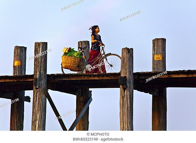 The BURMESE use the teak U BEIN BRIDGE to commute across the Taungthaman Lake at sunrise , Burma, Amarapura
