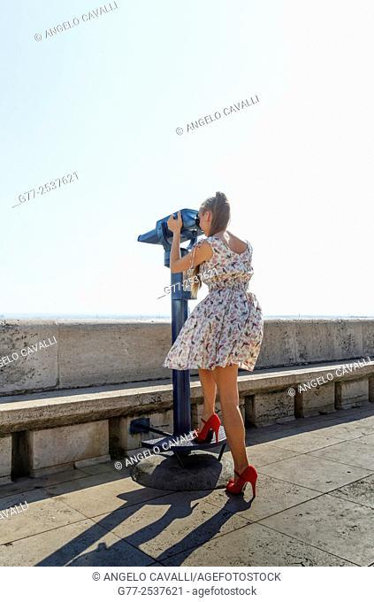 Woman using telescope. Budapest, Hungary