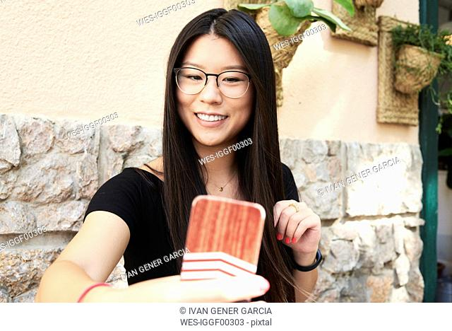 Asian young woman taking a selfie with her smartphone