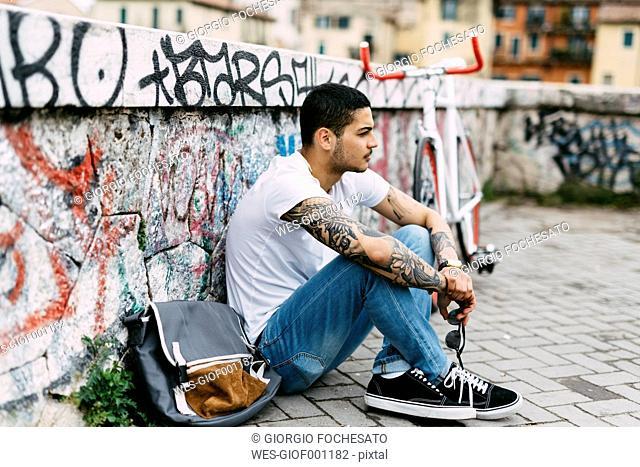 Young man sitting at graffiti wall