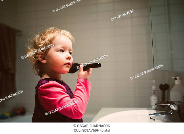 Cute girl looking in bathroom mirror applying blusher
