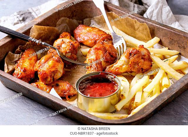 Fast food fried spicy chicken legs, wings and french fries potatoes with salt and ketchup sauce served on baking paper in old oven tray with kitchen towel and...
