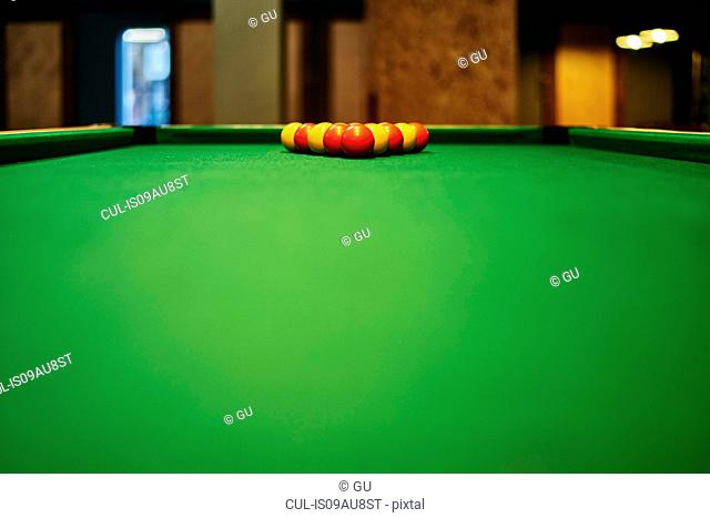 Surface level view of yellow and red pool balls on pool table