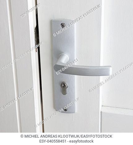 White door with chrome doorhandle, selective focus