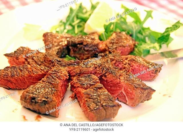 Grilled beef sirloin and salad on plate