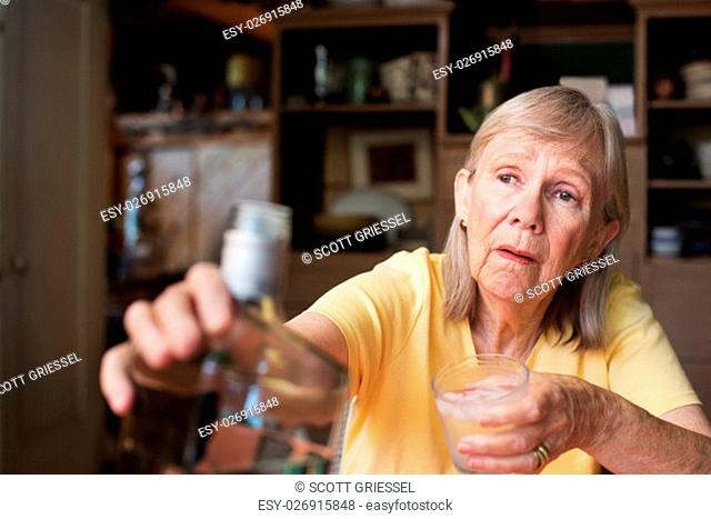 Lonely senior adult female reaching for a bottle of liquor while holding a glass