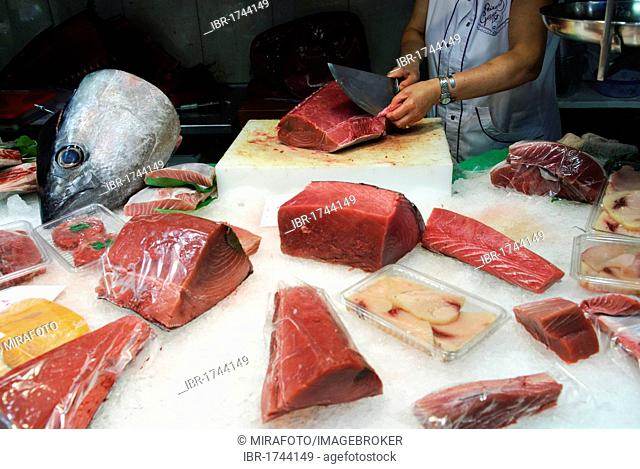 Woman cutting a large chunk of tuna at a fish stall where several pieces of tuna and a tuna head are displayed, indoor market hall Mercat de la Boqueria