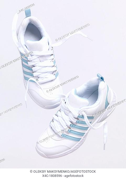 White sports shoes in mid air artistic still life isolated on white background