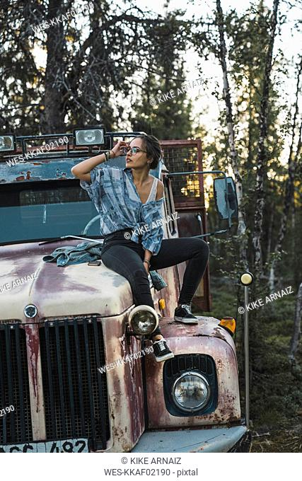 Young woman sitting on a broken truck
