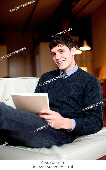 Businessman reading in armchair
