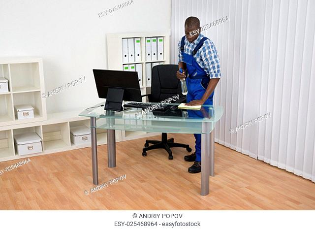 Young Male African Janitor Cleaning Desk With Cloth In Office