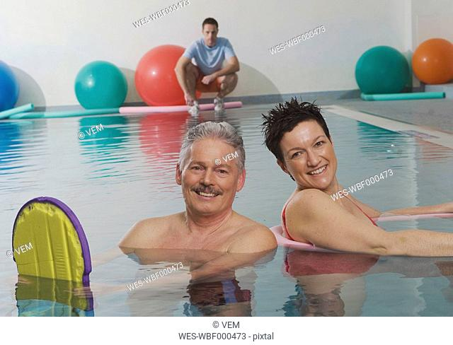 Germany, Nuremberg, Couple in pool with man in background