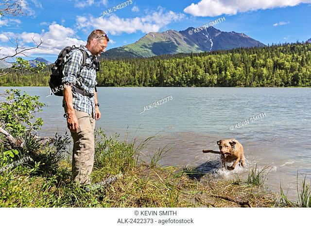 Male Hiker playing fetch with his dog at Trail lake with Kenai Mountains in the background, Summer, Moose Pass, Southcentral Alaska, USA