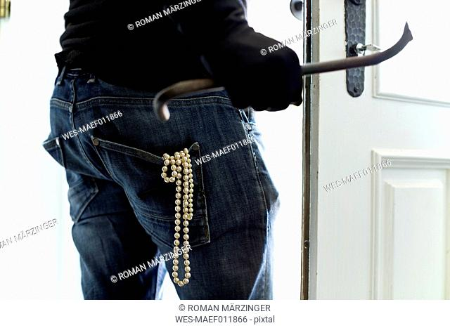Burglar with pearl necklace in pocket leaving house