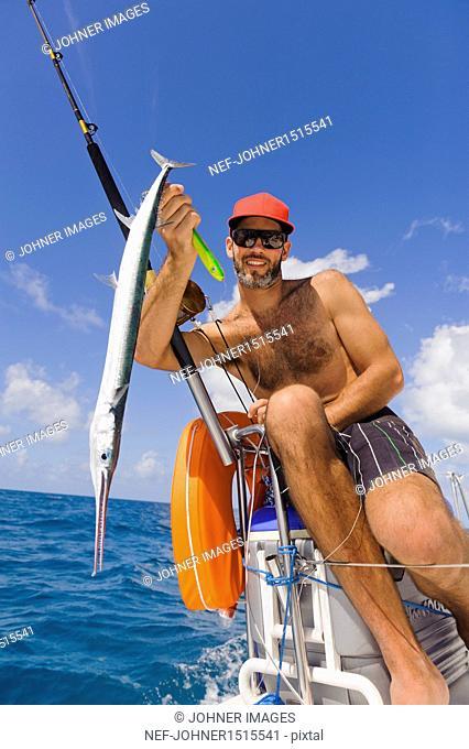 Mature man holding fish, focus on foreground