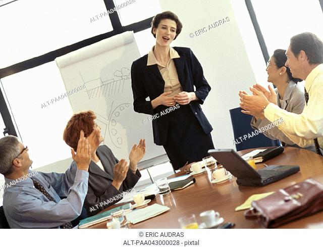 Group of business people in conference room, businesswoman being applauded