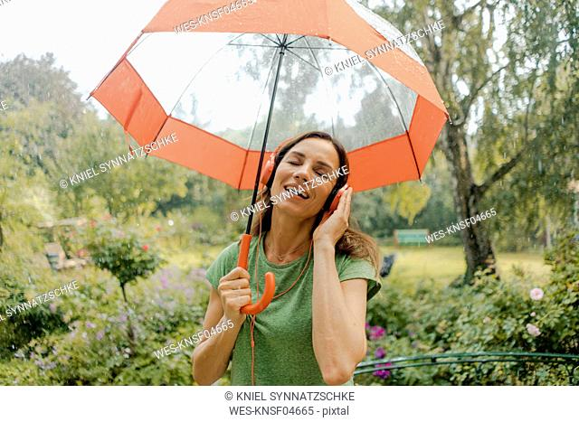 Happy mature woman standing in rain under umbrella listening to music with headphones