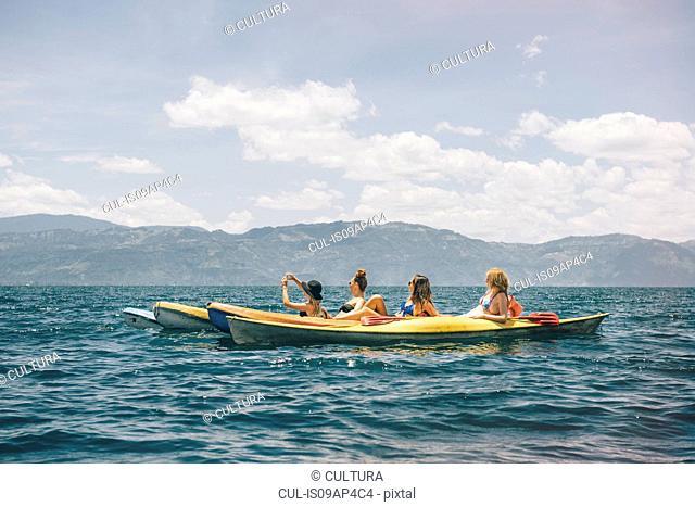 Four young female friends kayaking on Lake Atitlan, Guatemala