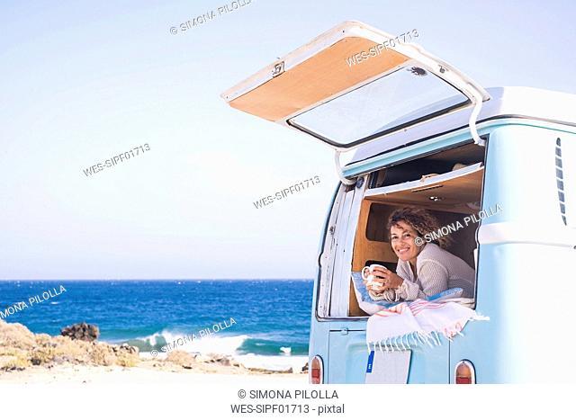 Spain, Tenerife, portrait of happy woman with coffee cup in van