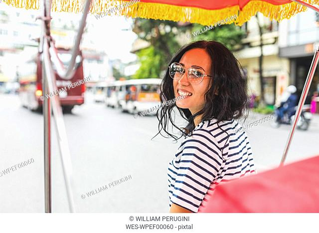 Vietnam, Hanoi, portrait of smiling young woman on a riksha in the city