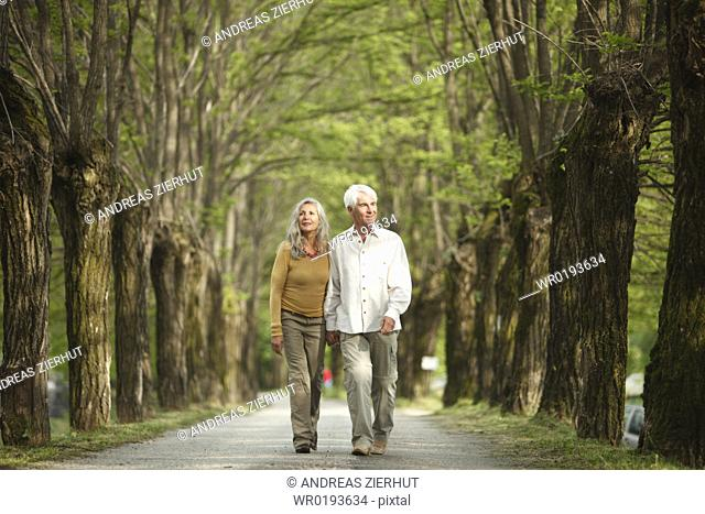 Senior couple walking hand in hand on a tree-lined road, Italy