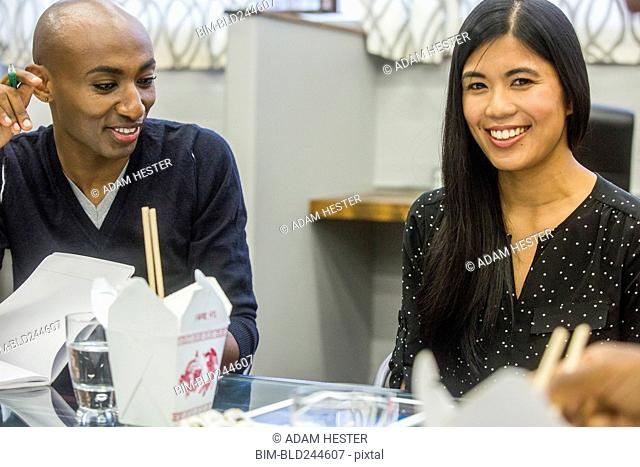 Smiling people in meeting with cartons of food