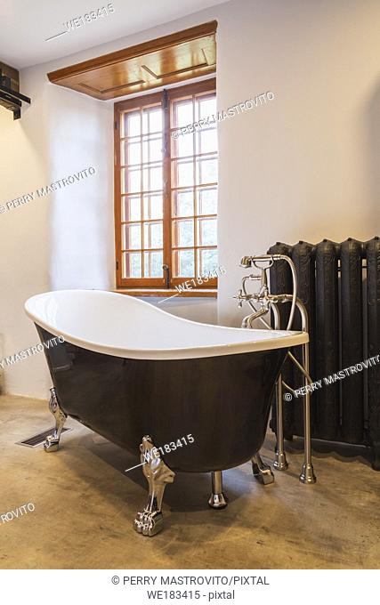 White and black freestanding chrome claw foot bathtub next to hot water heating radiator in main bathroom with birch tree bark imitation vinyl flooring inside...