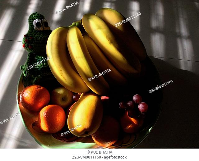 Light streaking through a Venetian blind illuminates a bowl with bananas, peaches, and other fruit, Ontario, Canada