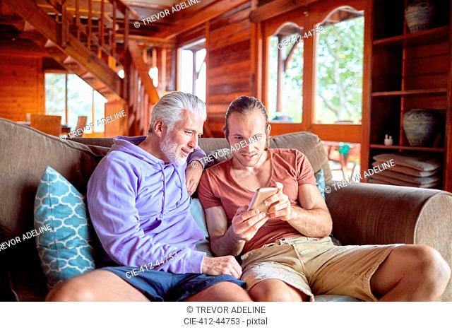 Father and son using smart phone on cabin sofa