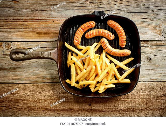 meat sausages and fried potatoes on cast iron pan, top view