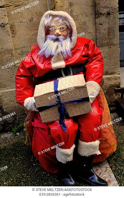 A fake Santa Claus outside a gift shop in December