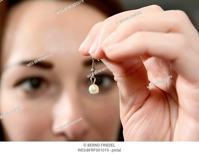 Young woman holding self-made earring