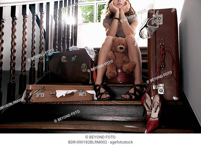 teenage girl sitting on stairs with teddy bear surrounded by suitcases