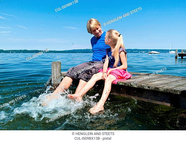 Father and daughter cooling feet in water, Lake Starnberg, Bavaria, Germany