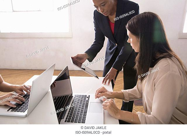 Women using laptop and digital tablet