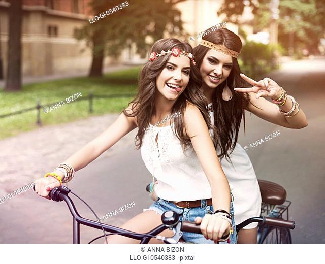 Portrait of funny boho girls on a tandem bicycle. Krakow, Poland