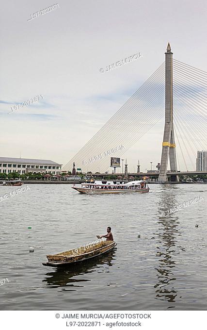 A fisherman catches fish in a small sampan, the Rama VIII bridge in the background, Bangkok Thailand