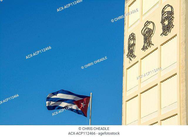 Cuban flag flies beside the offices of the Communist party building Havana, Cuba with representaions of heroes of the revolution