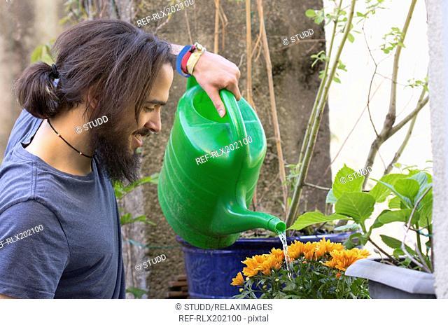 Side view of happy man watering plants on terrace