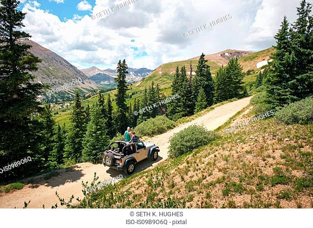 Road trip couple looking out at Rocky Mountains from four wheel convertible, Breckenridge, Colorado, USA