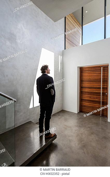 Pensive businessman standing in modern home showcase interior foyer