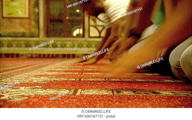 Young Muslim men kneeling and praying on carpet