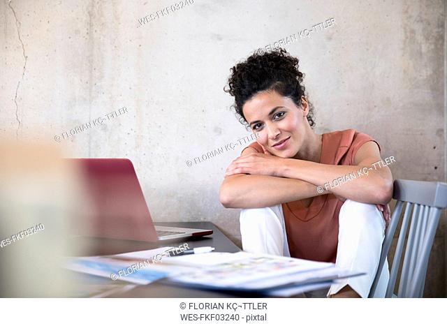 Portrait of smiling businesswoman sitting at table with documents and laptop