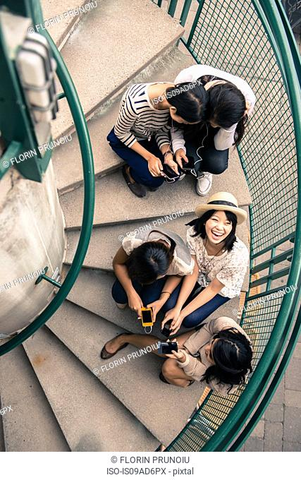 Five young women sitting on steps looking at smartphones