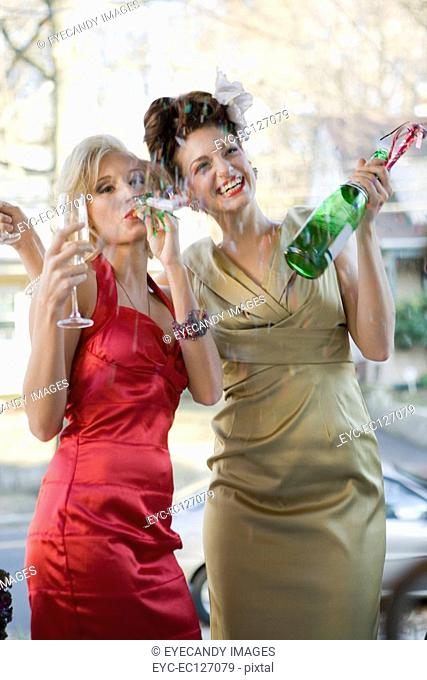 Portrait of happy women celebrating with champagne outdoors