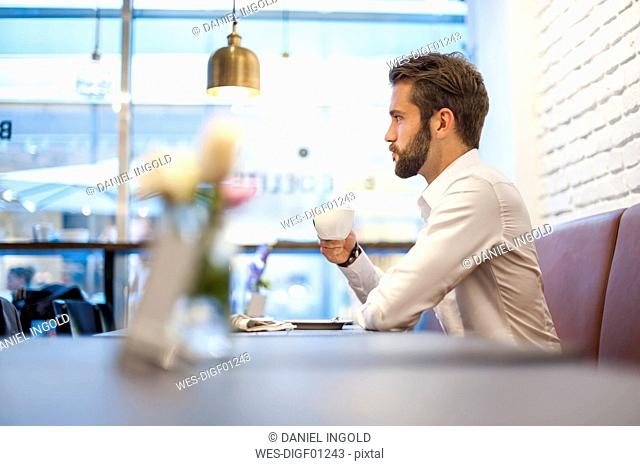 Businessman sitting in a cafe with cup of coffee